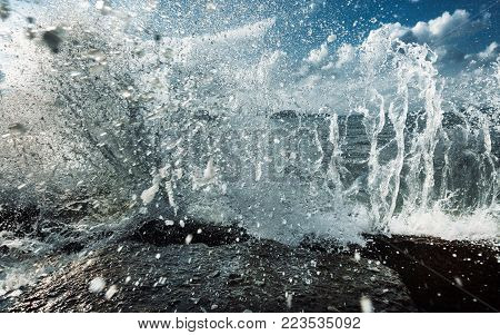 Large Waves Crash into Rock Tide pools, Throwing Foamy White Seawater Spray Into The Air In Storm