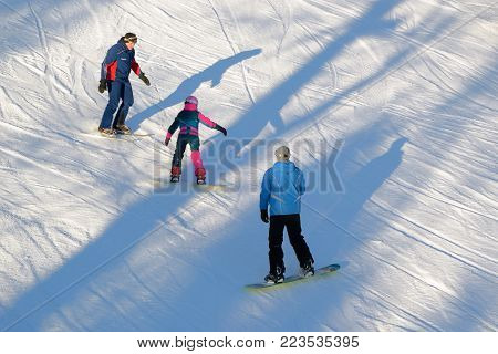 Stepanovo village, Russia - January 10, 2018: Instructors teach a child on a snow slope to snowboard