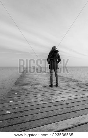a solitary woman looks at the sea from the pier