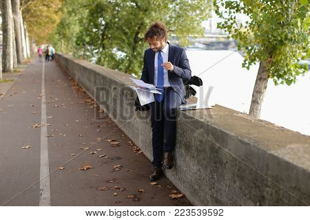 Young foreign boy planning study in France and reading instructions to exam candidates on laptop near Eiffel Tower.  Handsome Muslim guy sitting near river and dreaming. Attractive boy wears black suit and blue tie, has long curly hair and beard. Concept