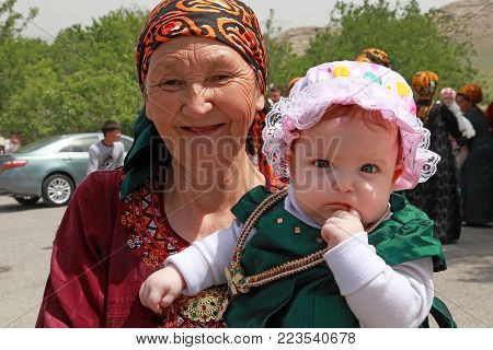 Kov-Ata, Turkmenistan - April 30, 2017: Grandmother with her granddaughter at a national wedding in the village of Kov-Ata. Turkmenistan - April 30, 2017.