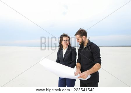 designer man and representative of investment company woman holding whatman paper with plan, people discussing spa-center in countryside. Bearded fair-haired guy and female in glasses smiling talking about project. Concept of international cooperation, ex