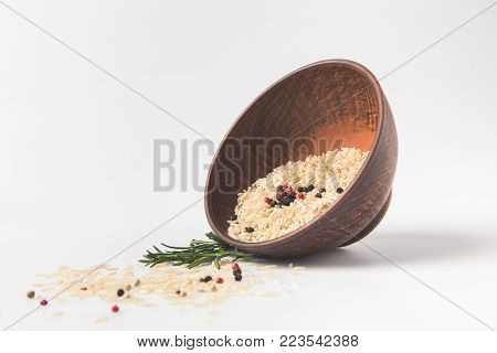 raw rice and peppercorns spilling out bowl on white surface
