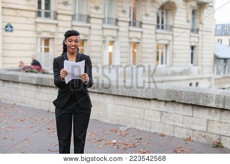 Actress got dream role in feature film. Happy African American with scenario in hands standing on street in big city and dancing. Young woman with black curly hair and bang wearing black jacket and trousers with white blouse. Concept progress in work, fav