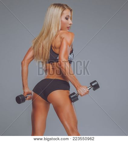 Blond fitness woman posing with dumbells over grey background.