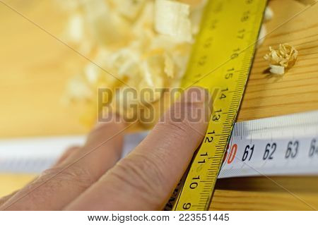 Close up of man marking wood with tape measure and square. Shallow depth of field.