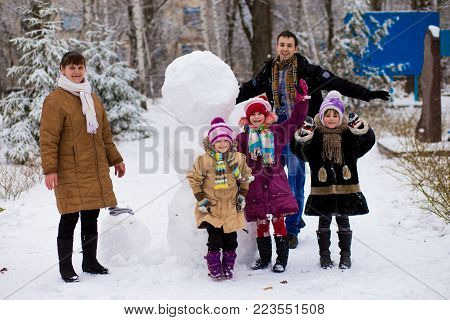 Big happy family: father, daughters and grandmother sculpt a big real snowman, Happy family have fun in a winter park