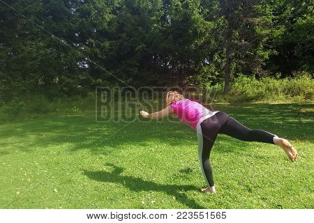 Middle aged yoga woman stretching and exercising outdoors.