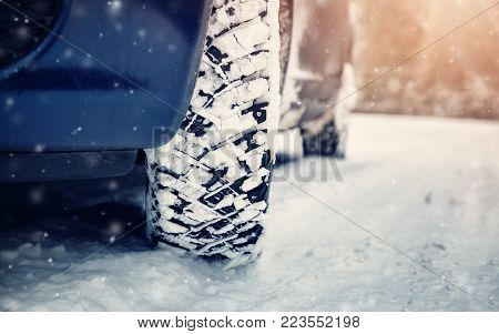 Car tires on winter road covered with snow. Vehicle on snowy way in the morning at snowfall