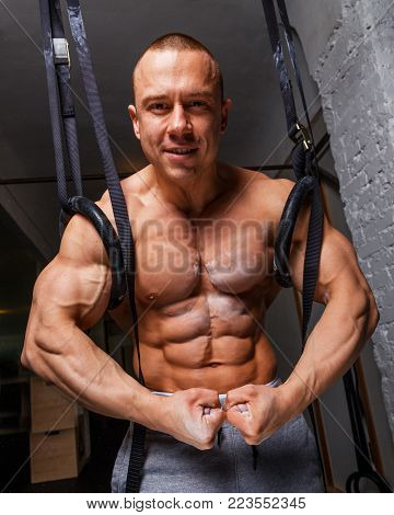 Strong muscular man bodybuilder poses and shows his abs and bicepses