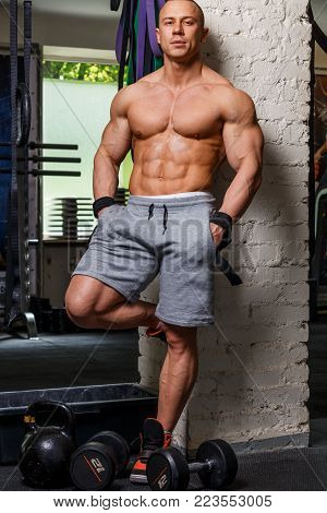 Strong muscular man bodybuilder poses and shows his trunk
