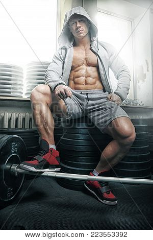 Strong muscular man bodybuilder sits on barbell plates