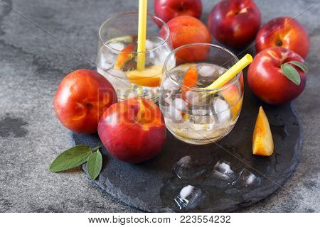 Summer diet cold drink: detox pure water with nectarine and ice, two glasses on dark background