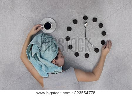 woman on a gray background lies and keeps a Cup of coffee and a round of cookies