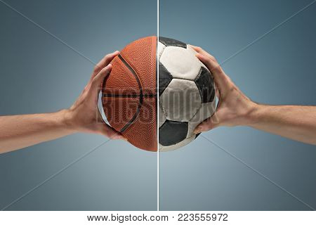 Hands holding soccer and basketball balls on gray studio background. concept of confrontation, differences in taste and preference