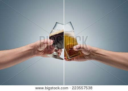 Closeup of a male hand holding up a glasses of dark and light beer over a blue background. concept of confrontation, differences in taste and preference
