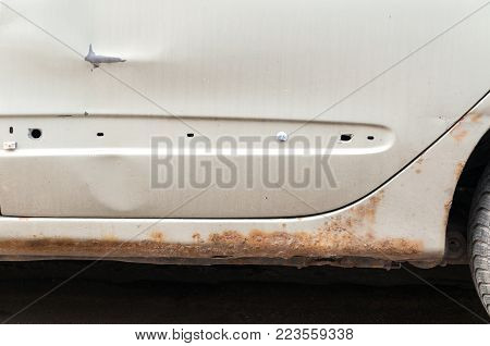 Damaged car. Damaged white car with scratched paint and rust with holes at the bottom of the floor