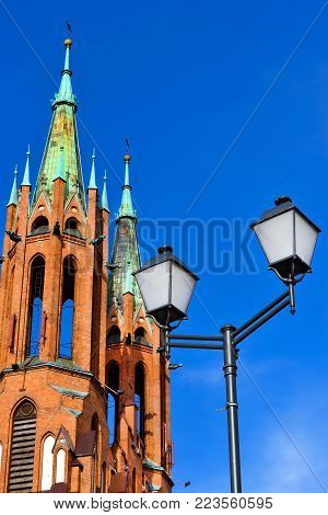 Street lamp in background of Cathedral Basilica of Assumption of Blessed Virgin Mary in Bialystok, Poland. Gothic architecture of red brick - religious memorial and place of worship