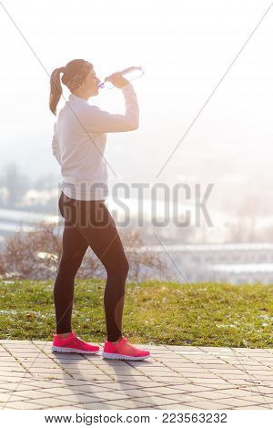 Woman drinking water during a running. Cold weather. Jogging woman in a city during a winter. Sunny day. Drinking mode.