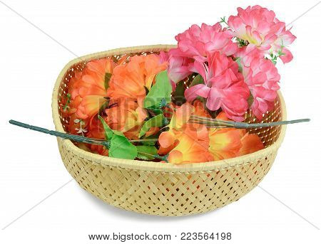 In the basket, the three branches of Artificial flowers rose peony red white yellow and orange bright color made of synthetic fabric and plastic. Items pictured close up isolated on white background.