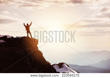 Hiker or traveller stands in winner pose at mountain top against mountains and sunset. Win or success concept