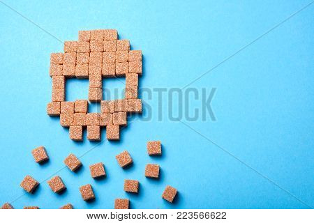 A lot of sugar kills people. Skull of cubes of cane brown sugar. Copy space for text