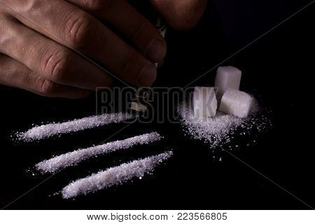 Sugar addict. Addiction of sweets and fast carbohydrates. A line of white sugar sniffs a man through the dollar like cocaine. Dark background