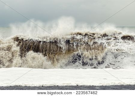 Storm on the sea - a big wave with sand and foam rises near the shore. Stress and restless concept.