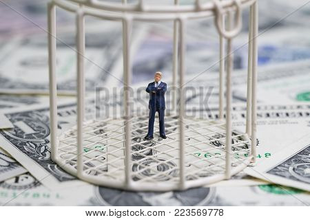 Miniature businessman inside birdcage on pile of dollar banknotes metaphor of inside the box thinking or money trap.