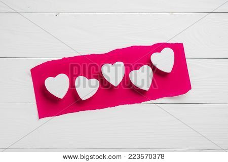 Decorative white wooden hearts on crimson paper and on the wooden background. Greeting card template for wedding or Valentines day. Wooden Background for design to Valentine's Day.