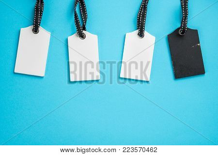 Empty white and  black tags in a row on blue background. Top view. Mock up sample. Blank price tag. Design for shopping label template, discount, Sale. Sales tags.