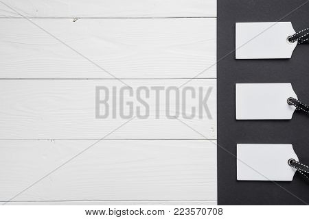 Empty white tags in a row on white and black wooden background. Top view. Mock up sample. Blank price tag on wooden planks. Design for shopping label template, discount, Sale. Sales tags.