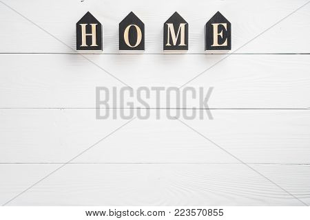 Word home on white wooden background with copy space. Home word concept. Home word written on black wooden houses.