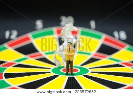 Miniature people, moderator standing with horse on dartboard background using as business and speech concept