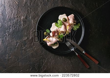 Vitello tonnato italian dish. Thin sliced veal with tuna sauce, capers and coriander served on black plate with fork and knife over dark texture background. Top view, copy space