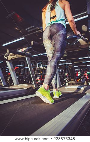 Theme of sport and weight loss. A view from bottom of the foot of young strong woman in light green sneakers and tights on a simulator, running at the gym. Preheating before training, cardio training.