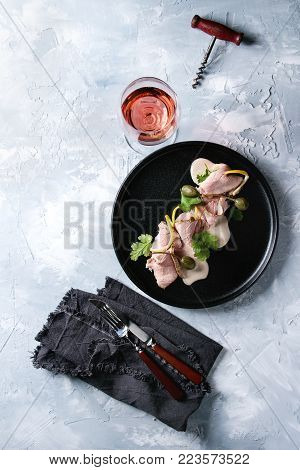 Vitello tonnato italian dish. Thin sliced veal with tuna sauce, capers and coriander served on black plate, glass of rose wine, cutlery on textile napkin over gray texture background. Top view, space