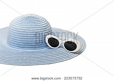 Summer woman's hat and sunglasses of blue and white color on isolated background. Selective focus.