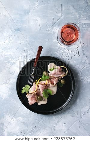 Vitello tonnato italian dish. Thin sliced veal with tuna sauce, capers and coriander served on black plate with fork and glass of rose wine over gray texture background. Top view, space