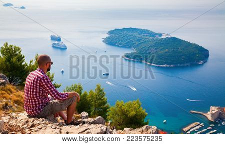 man looking down to the island Lokrum near Dubrovnik, sitting on the mountain above the city, Croatia