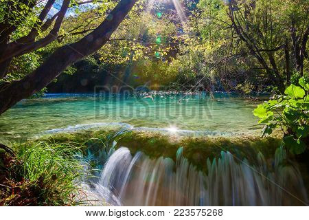 small waterfall with sunlight rays in Plitvice National Park, Croatia
