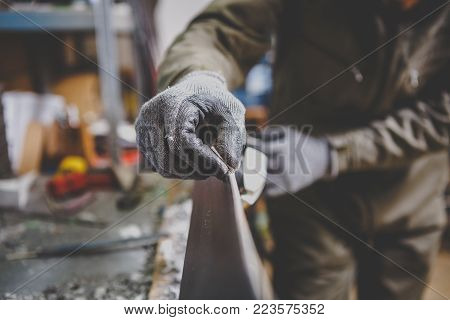 A man repairman in workshop ski service repairing the sliding surface of the ski at Ski vise. In hands of instrument Final edge sharping by gummy stone. Theme ski repair and maintenance of equipment.