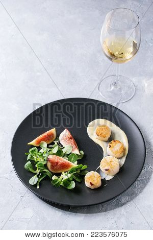 Fried scallops with lemon, figs, sauce and green salad served on black plate with glass of white wine over gray texture background. Plating, fine dining