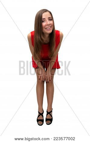 Sexy happy laughing girl in red dress in stockings and in high heels shoes is bending her knees and bending forward isolated on white background.