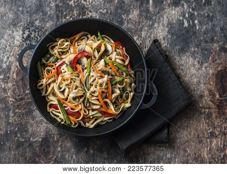 One pan yaki udon noodles with stir fry vegetables. Vegetarian noodles with green beans, sweet peppers, mushrooms, carrots - healthy foods for lunch on a wooden background, top view