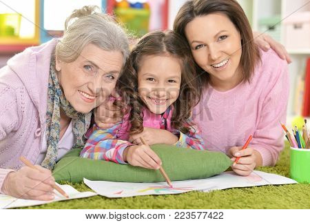 three generations of women from one family lying on floor and drawing picture together