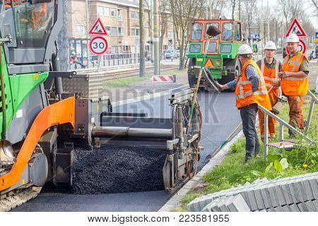 Laan van meerdervoort, The Hague, the Netherlands - 31 march 2017: road work team laying blacktop to resurface new road