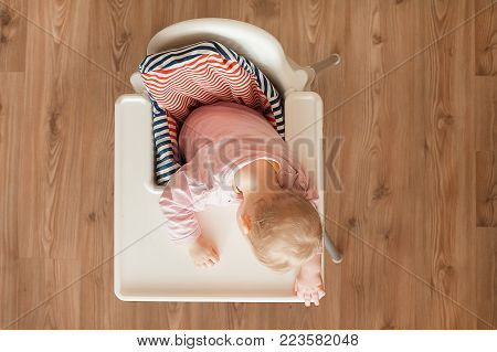 Tired child sleeping in highchair after the lunch. Cute baby girllying his face on the table tray.  Top view.