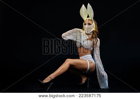 Sexy girl in white lingerie and LED mask. Go-go dancer. Stripper in the studio on a black background. A girl from the show ballet in the night club.