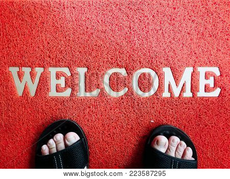 Red mat with welcome word and foot